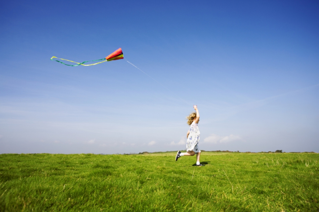A young girl flying her kite       Copyright