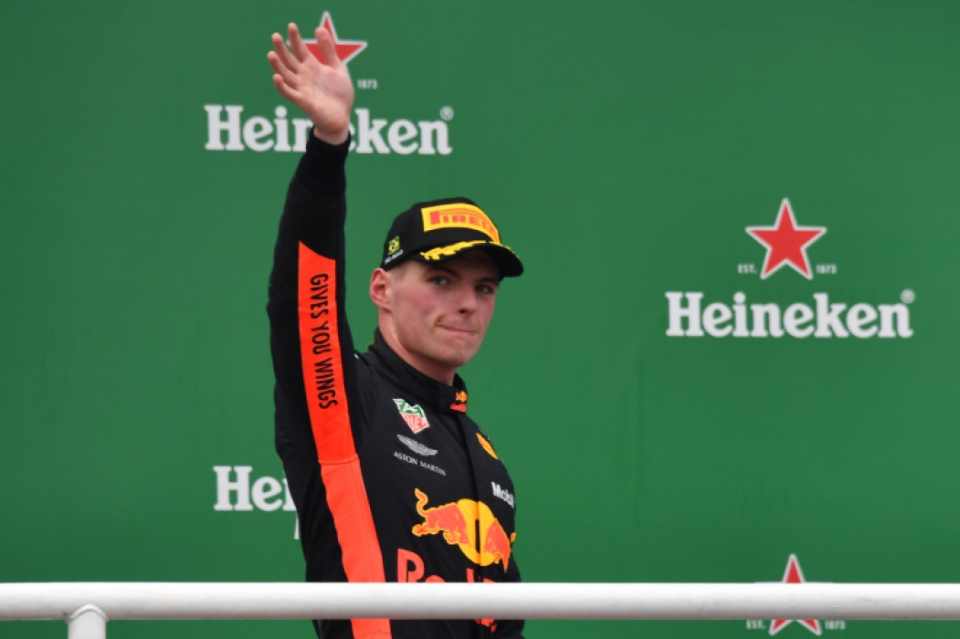 F1 Brazil Grand Prix runner-up Red Bull's Dutch driver Max Verstappen waves at the crowd as he gets onto the podium at the Interlagos racetrack in Sao Paulo, Brazil on November 11, 2018. - Lewis Hamilton won the Brazilian Grand Prix on Sunday as his Mercedes team added the constructors title to the British driver's fifth world crown. Verstappen in a Red Bull was second with Ferrari's Kimi Raikkonen in third. (Photo by Nelson ALMEIDA / AFP)