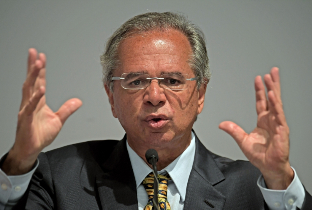 The new Brazilian Economy Minister, Paulo Guedes speaks during a ceremony in which he took office in Brasilia, on January 02, 2019. - Brazl's President Jair Bolsonaro has appointed a free-marketeer, Paulo Guedes, as economy minister to push through reforms to bring down Brazil's swelling debt, mainly through privatizations, tax changes and encouraging foreign investment. (Photo by CARL DE SOUZA / AFP)       Caption