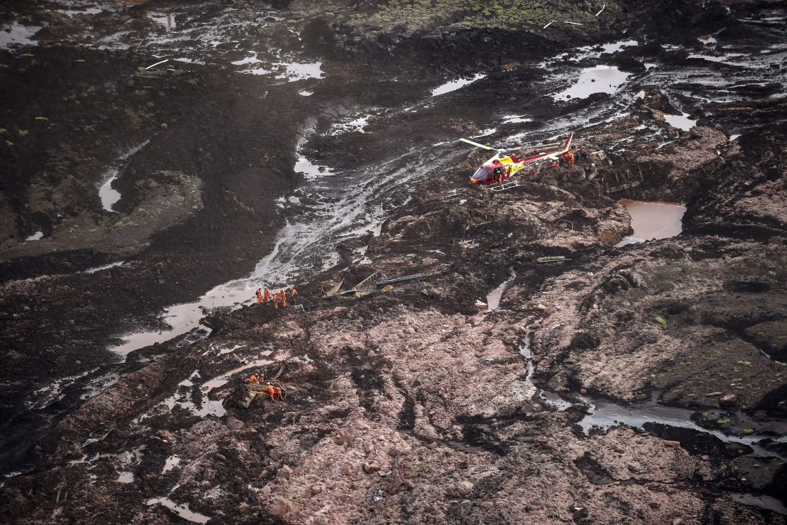 A firefighters' helicopter overflies the area as rescuers work in the search for victims after the collapse of a dam, which belonged to Brazil's giant mining company Vale, near the town of Brumadinho in southeastern Brazil, on January 25, 2019. - A dam collapse in southeast Brazil unleashed a torrent of mud on a riverside town and surrounding farmland Friday, destroying houses, leaving 200 people missing and raising fears of a number of deaths, according to officials. (Photo by Douglas Magno / AFP)