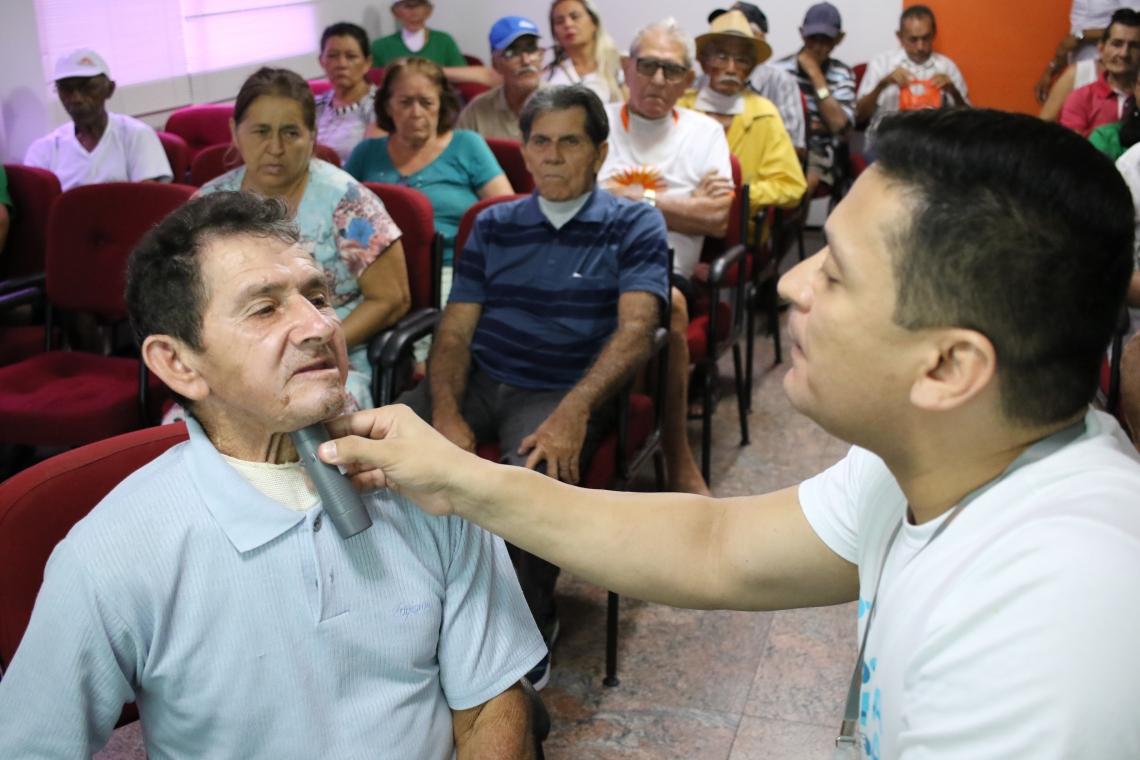 Raimundo Napoleão Abreu, 62, faz o teste da laringe eletrônica pela primeira vez com ajuda de fonoaudiólogo (Foto: Fábio Lima/O POVO)