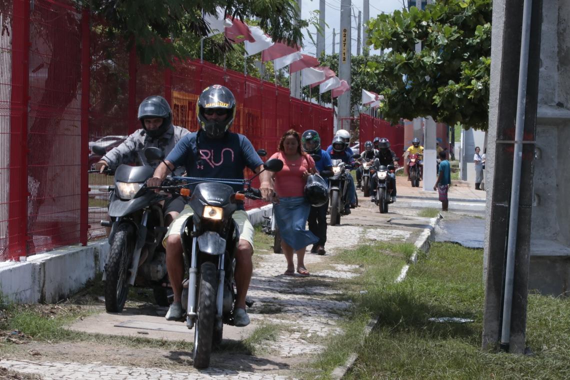 Motociclistas fugindo do trecho alagado transitando por cima da calçada (Gustavo Simão/ Especial para O POVO)
