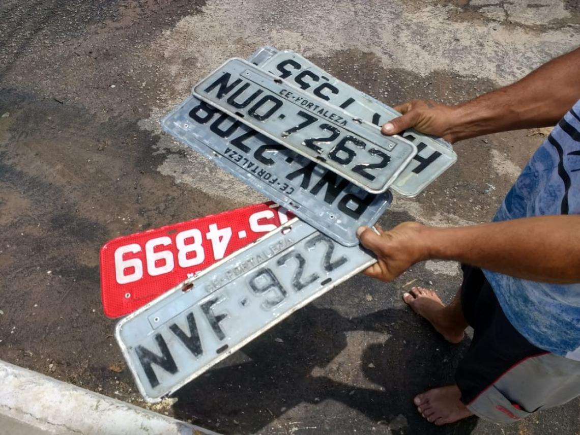 Placas que caiam de carros quando passavam no alagamento eram guardadas por jovens que ajudavam no trânsito(Alexia Vieira/Especial para O POVO)
