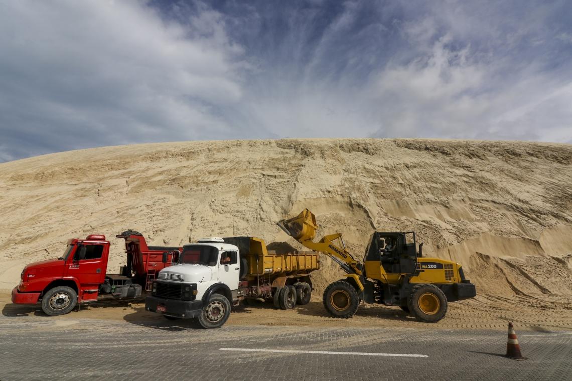 Com auxílio de trator, caminhões fazem a remoção da areia das dunas da Sabiaguaba. (Foto: Mateus Dantas / O POVO)