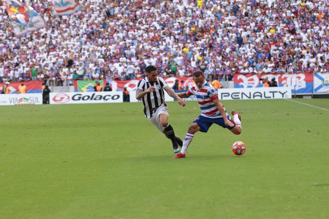 Carlinhos (à direita), em disputa com Leandro Carvalho durante o Clássico-Rei de domingo
