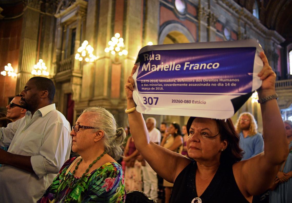 Uma mulher segura uma placa que homenageia Marielle em missa na Igreja da Candelária