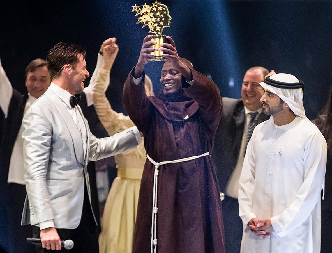 Peter Tabichi, ao centro, recebeu o prêmio de um milhão de dólares em cerimônia apresentada pelo ator australiano Hugh Jackman, o Wolverine da franquia X-Men (à esquerda)