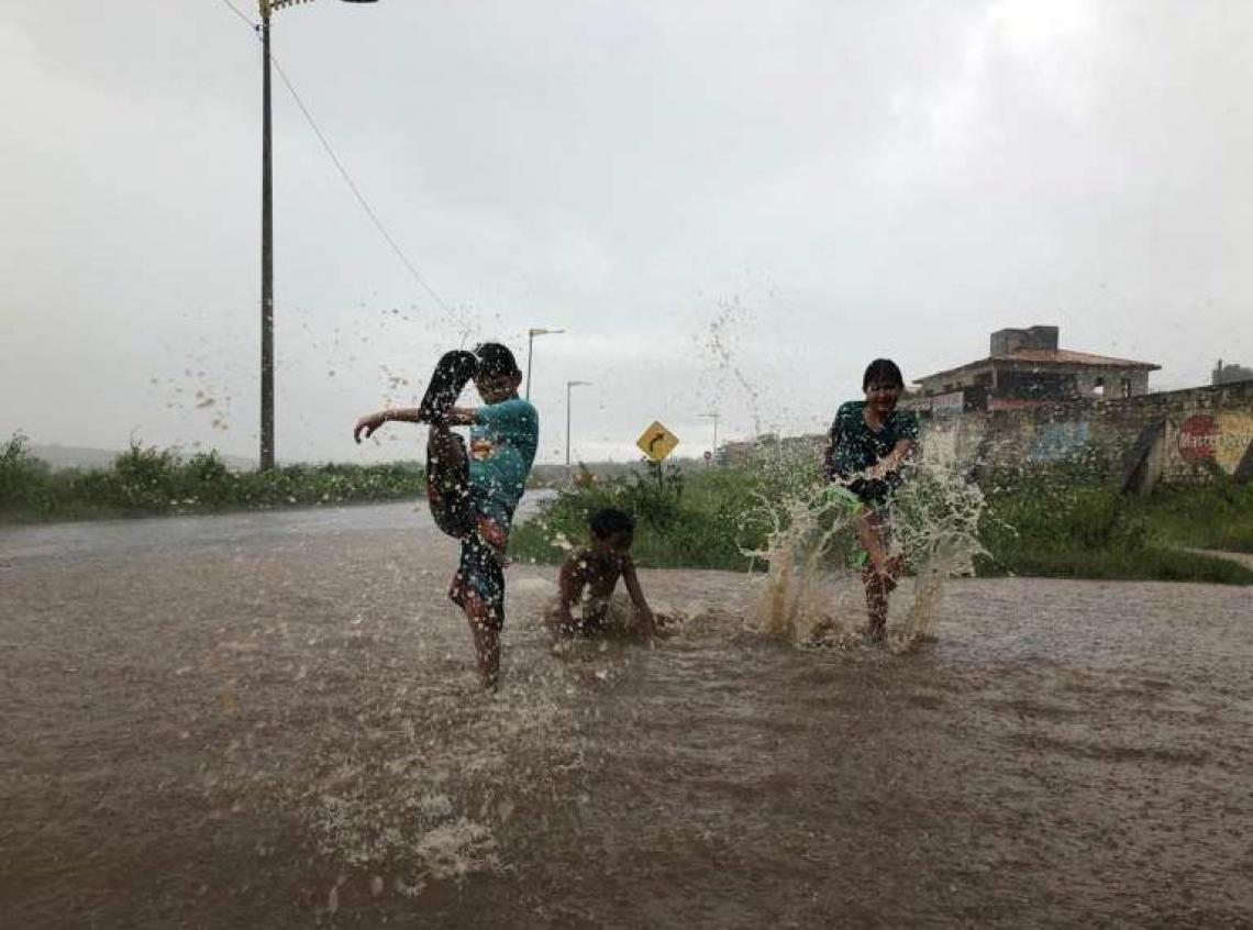 Crianças do Município de Lavras da Mangabeira, onde registrou 148,6 mm de chuva no final de semana, aproveitaram a água acumulada para brincar.