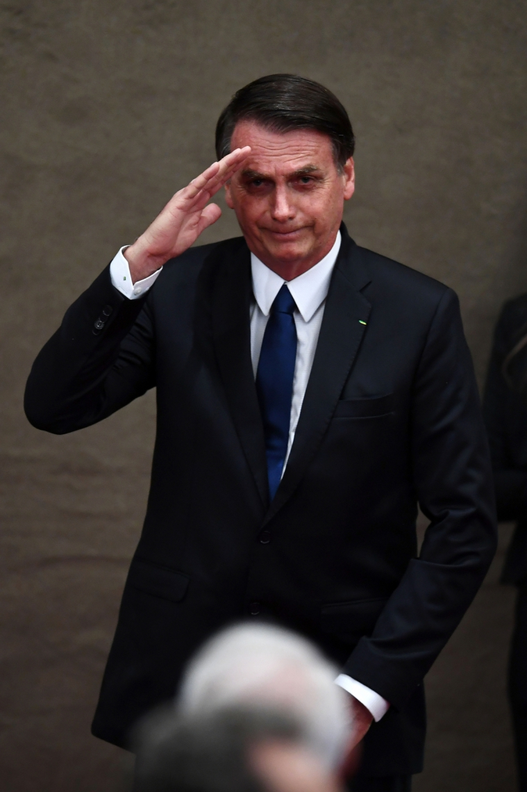 Brazilian President-elect Jair Bolsonaro salutes during a ceremony in which he received a diploma that certifies he can take office as president from Electoral Supreme Court (TSE) president Justice Rosa Weber, at the TSE in Brasilia, on December 10, 2018. - Bolsonaro takes office on January 1, 2019. (Photo by EVARISTO SA / AFP)
