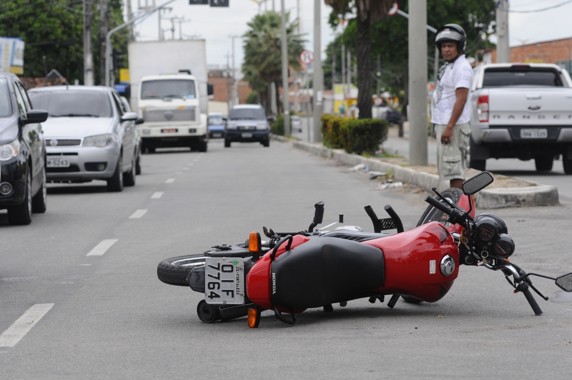 Moto caída após acidente. Colisão entre uma moto e um veículo no cruzamento na avenida Silas Munguba com rua Teixeira Leite.