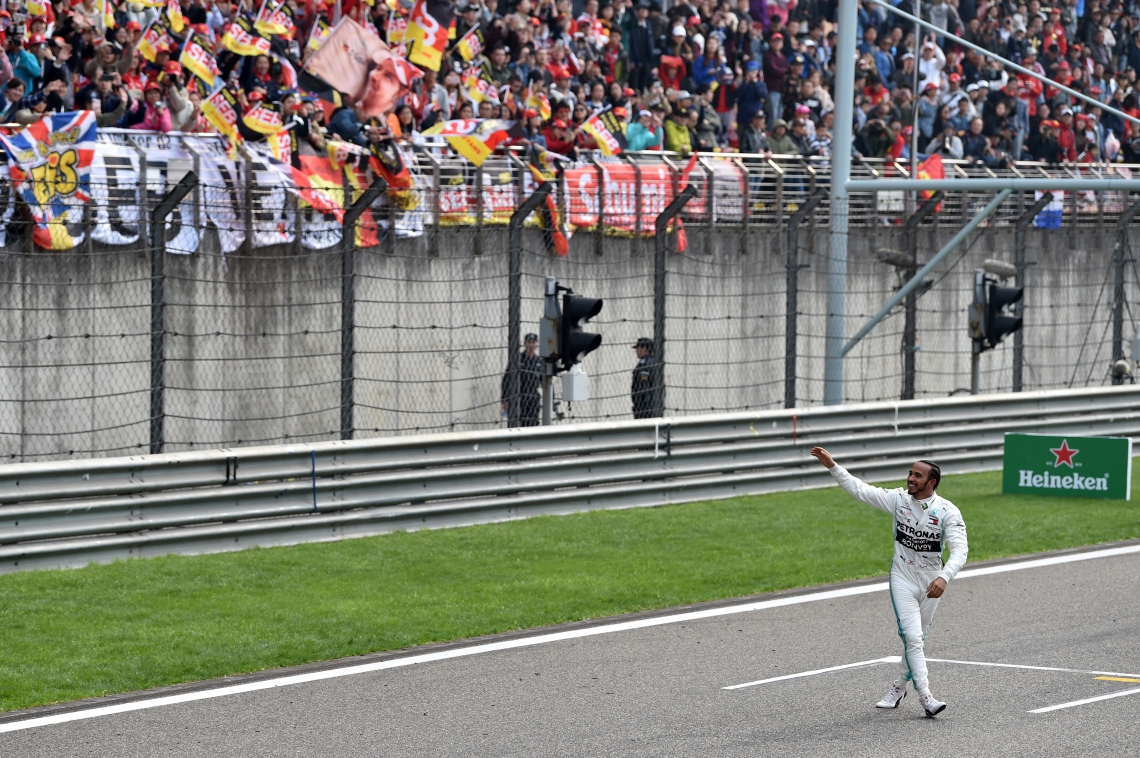 Mercedes' British driver Lewis Hamilton waves to fans after winning the Formula One Chinese Grand Prix in Shanghai on April 14, 2019. (Photo by STR / AFP)