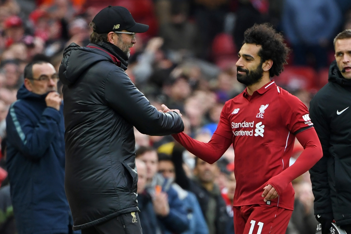 Liverpool's Egyptian midfielder Mohamed Salah (R) shakes hands with Liverpool's German manager Jurgen Klopp (L) as he's substituted during the English Premier League football match between Liverpool and Chelsea at Anfield in Liverpool, north west England on April 14, 2019. - Liverpool won the game 2-0. (Photo by Paul ELLIS / AFP)