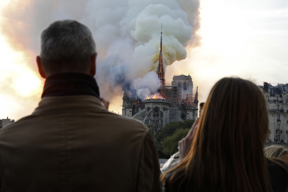People react as they watch flames engulf the roof of the Notre-Dame de Paris Cathedral in the French capital Paris on April 15, 2019. - A colossal fire swept through the famed Notre-Dame Cathedral in central Paris on April 15, 2019, causing a spire to collapse and threatening to destroy the entire masterpiece and its precious artworks. The fire, which began in the early evening, sent flames and huge clouds of grey smoke billowing into the Paris sky as stunned Parisians and tourists watched on in sheer horror. (Photo by GEOFFROY VAN DER HASSELT / AFP)