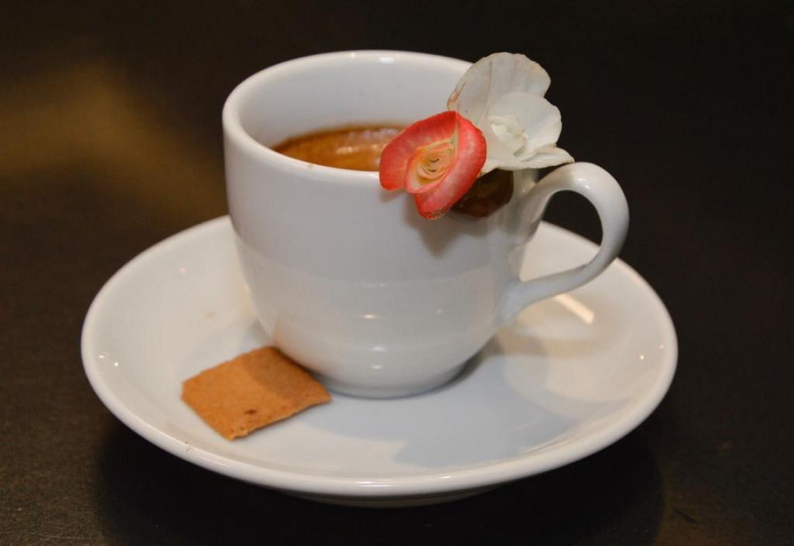 O café servido é acompanhado de uma flor comestível