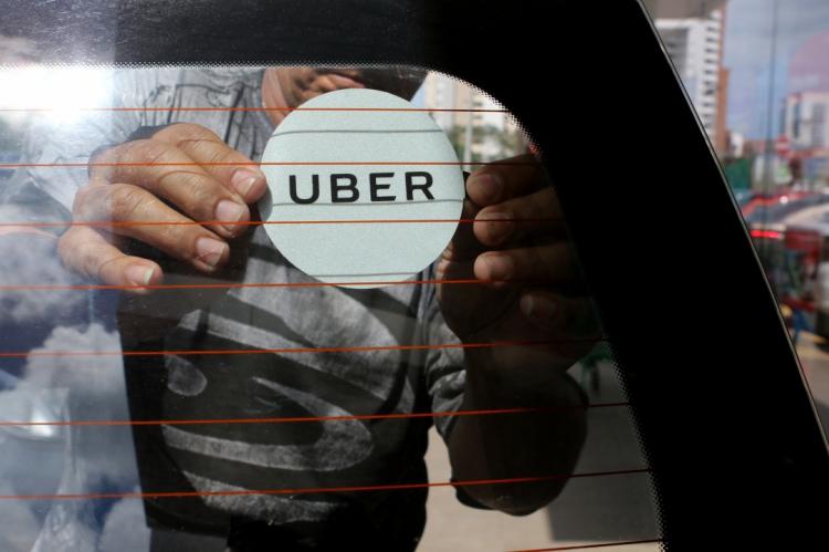 Motoristas do aplicativo Uber fazem fila na frente da sede da empresa para colocar adesivo obrigatório