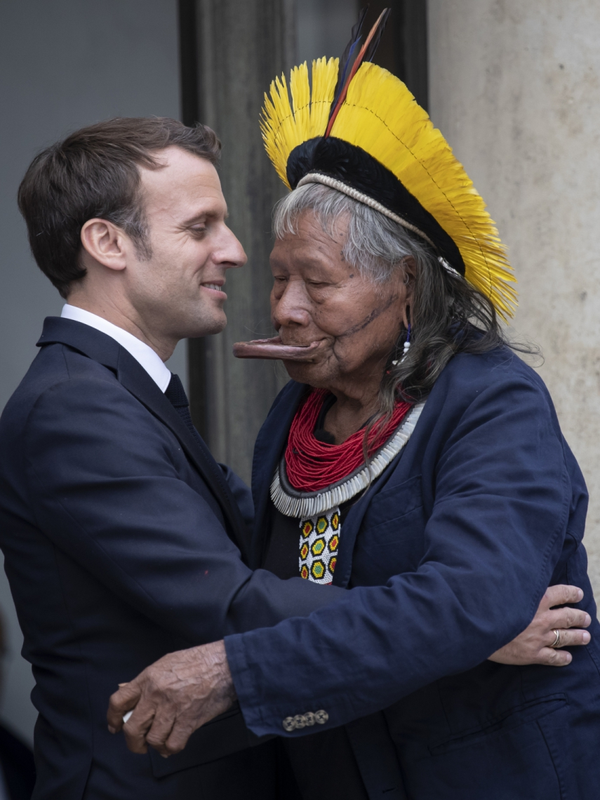 Brazil's legendary indigenous chief Raoni Metuktire (R) embraces French President Emmanuel Macron (L) after their meeting at the Elysee Palace on May 16, 2019 in Paris, part of the Brazilian leader's three-week tour across Europe where they will meet heads of state, celebrities and the Pope to highlight growing threats to the Amazon. - The elderly Kayapo chief, internationally recognisable through his traditional lip plate and feather headdress, will seek to raise one million euros (1,1 million USD) to better protect the Amazon's Xingu reserve, home to many of Brazil's tribal peoples, from loggers, farmers and fire. (Photo by Thomas SAMSON / AFP)