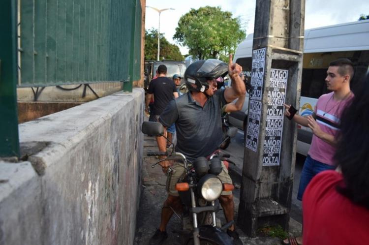 Na mão direita o homem portava uma arma de fogo, que utilizou para ameaçar os manifestantes