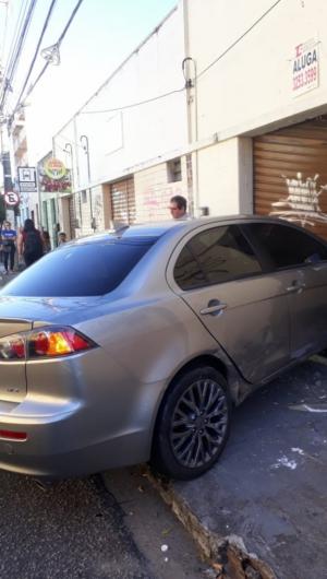 Frente do carro de modelo Lancer, portão e parte da parede do prédio ficaram danificados