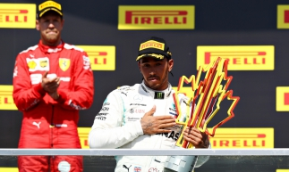 MONTREAL, QUEBEC - JUNE 09: Race winner Lewis Hamilton of Great Britain and Mercedes GP celebrates on the podium as second placed Sebastian Vettel of Germany and Ferrari applauds during the F1 Grand Prix of Canada at Circuit Gilles Villeneuve on June 09, 2019 in Montreal, Canada.   Mark Thompson/Getty Images/AFP       Caption