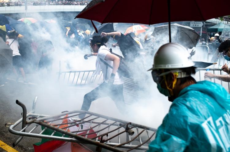 Manifestantes correm após a polícia ter disparado gás lacrimogêneo durante uma manifestação contra uma polêmica proposta de lei de extradição fora da sede do governo em Hong Kong