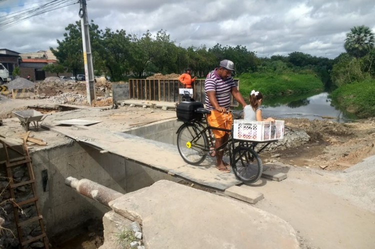José Maria Oliveira e sua filha atravessam a ponte na Rua Holanda, na Maraponga.
