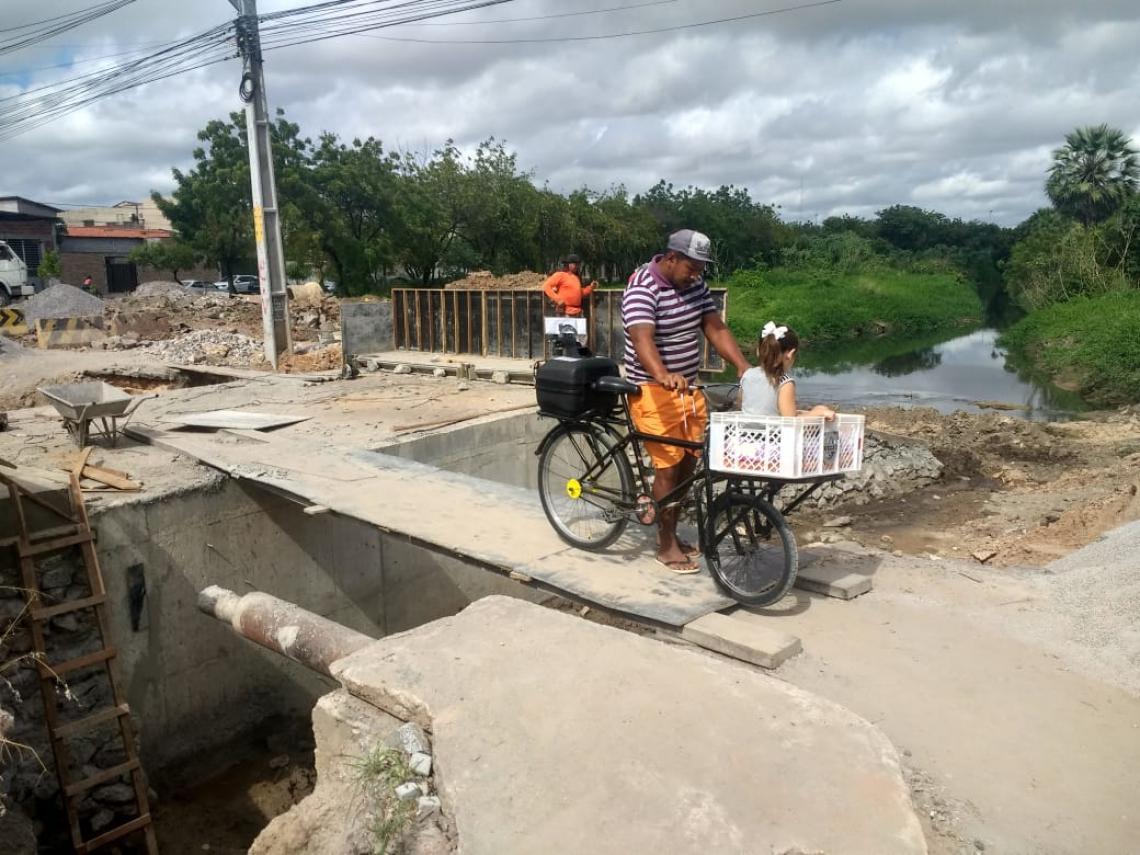 José Maria Oliveira e sua filha atravessam a ponte na Rua Holanda, na Maraponga, antes das obras