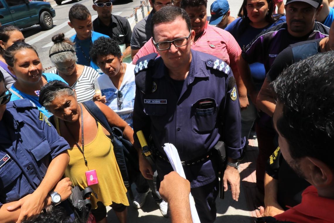 Representante da guarda municipal conversa com manifestantes.