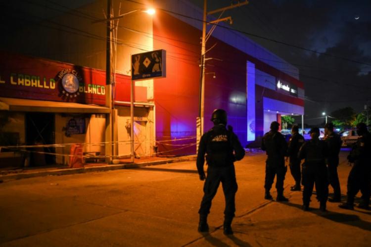 Policiais interditam o entorno do bar incendiado.