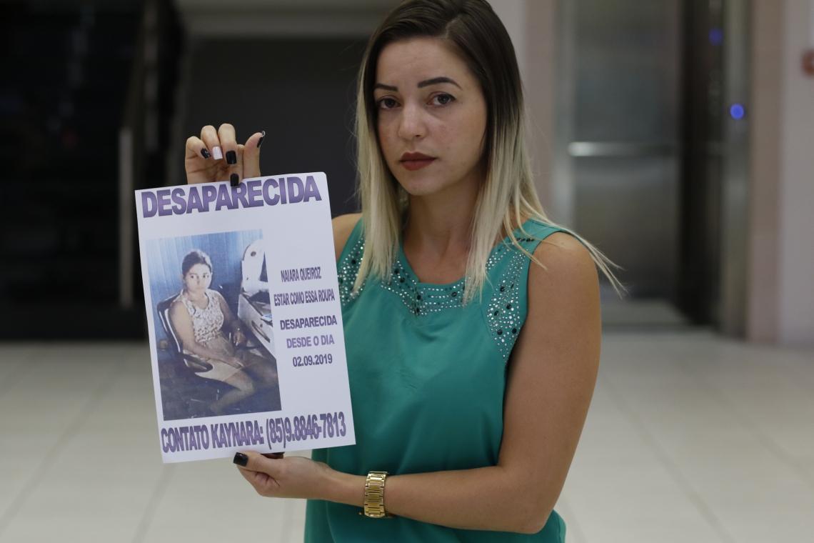 Kaynara Lima exibe cartaz com a foto da irmã Naiara Lima, que estava desaparecida