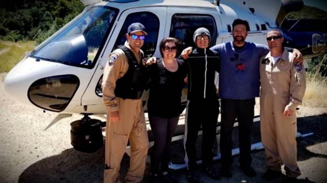 Krystal Ramirez (à esquerda), Hunter Whitson (ao centro) e Curtis Whitson (à direita) posam para foto com equipe de resgate.