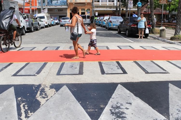 Tapete vermelho é estendido sobre faixa de pedestre para ação educativa sobre mobilidade, na Praça do Ferreira.