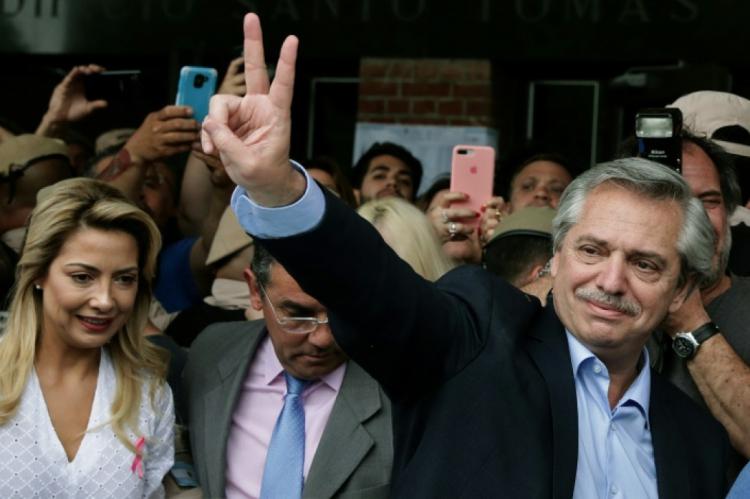 O candidato peronista à Presidência argentina Alberto Fernández (D) faz o sinal da vitória ao deixar sua seção eleitoral após votar em Buenos Aires, 27 de outubro de 2019