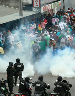 """Riot police fire tear gas as supporters of the Movimiento Al Socialismo (MAS) party, of Bolivian President Evo Morales, confront supporters of the Comunidad Ciudadana (CC) opposition party, of former presidential candidate Carlos Mesa, during a strike in Santa Cruz on October 28, 2019. - The platform gathering the regional civic committees (Conade), demanded the annulment of the controversial general elections in Bolivia, won by President Evo Morales in the first round, and called for new elections with a new electoral court. (Photo by DANIEL WALKER / AFP) / """"The erroneous mention appearing in the metadata of this photos by DANIEL WALKER has been modified in AFP systems in the following manner: [in Santa Cruz] instead of [in La Paz]. Please immediately remove the erroneous mention from all your online services and delete them from your servers. If you have been authorized by AFP to distribute it (them) to third parties, please ensure that the same actions are carried out by them. Failure to promptly comply with these instructions will entail liability on your part for any continued or post notification usage. Therefore we thank you very much for all your attention and prompt action. We are sorry for the inconvenience this notification may cause and remain at your disposal for any further information you may require."""""""