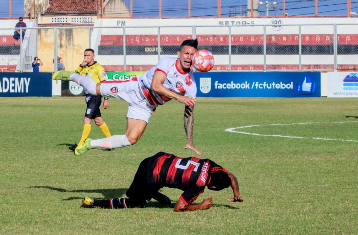 Siloé (pulando) disputando a bola com Bruno Ocara (carrinho).