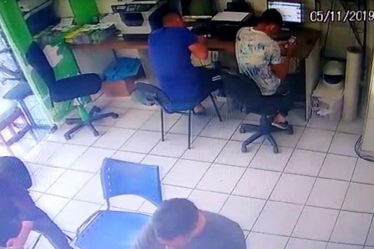Policial estava sentado de camisa azul.