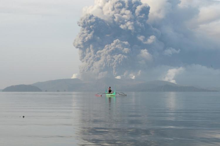 Jovem em canoa com o vulcão Taal ao fundo, em 13 de janeiro