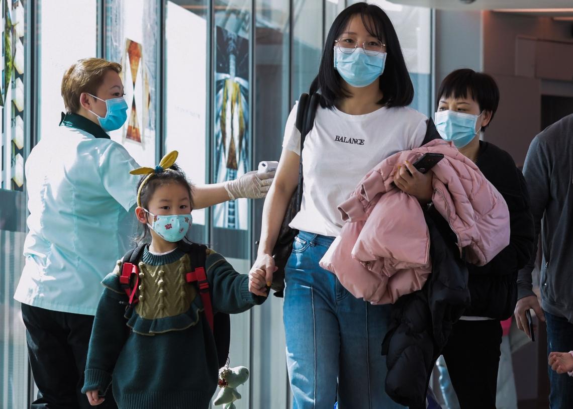 Um oficial de saúde (L) analisa os passageiros que chegam da China no aeroporto internacional de Changi, em Cingapura, em 22 de janeiro de 2020, conforme as autoridades aumentam a medida contra o coronavírus.