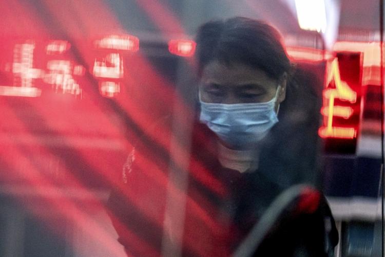 Mulher usando uma máscara protetora em  Pequim. Na Cidade, foi ordenado o fechamento de escolas do ensino fundamental e secundárias. (Foto: NICOLAS ASFOURI /AFP)
