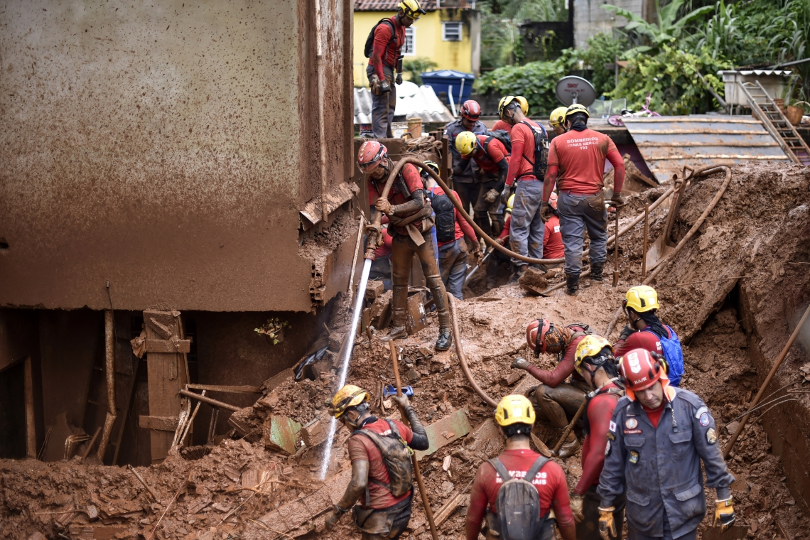 Firefighters search for missing persons using a hydraulic dismantling technique, which uses water to disperse mud, after a landslide in Vila Bernadete, Belo Horizonte, Minas Gerais state, Brazil, on January 26, 2020. - A landslide buried several houses in Vila Bernadete Friday, leaving 4 dead and 7 missing. Two days of torrential rains in Minas Gerais state have left at least 30 people killed, several injured, 17 missing and more than 2,500 homeless following a series of landslides and house collapses, Civil Defence officials said. (Photo by DOUGLAS MAGNO / AFP)