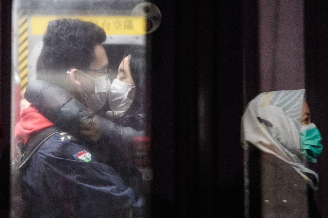 27-01-2020, um casal usando máscaras beija-se em um trem de metrô subterrâneo enquanto outro passageiro (R) é refletido em uma porta de vidro de plataforma durante um feriado público do Ano Novo Lunar do Rato em Hong Kong , como medida preventiva após um coronavírus surto que começou na cidade chinesa de Wuhan. (Foto: Anthony WALLACE / AFP)