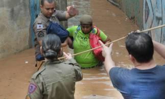 Policiais ajudam a resgatar vítimas em áreas alagadas. Há resistência de moradores em deixar áreas de risco