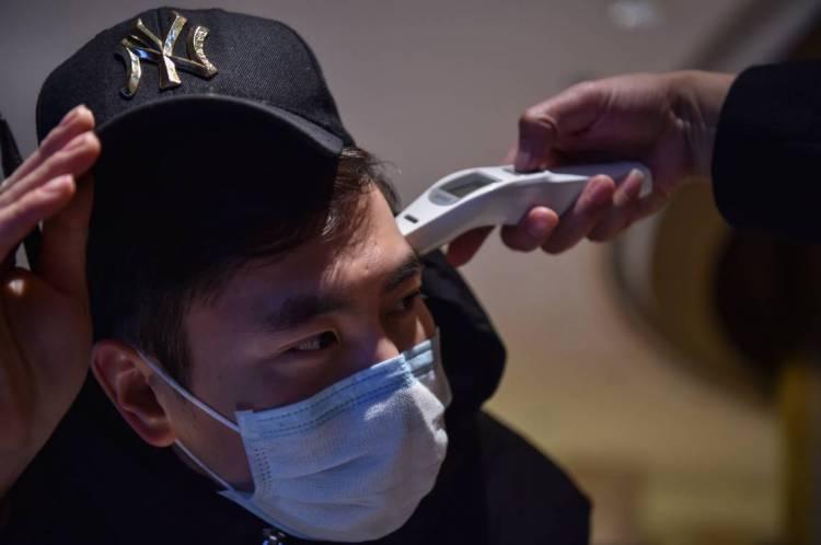China, 24 de janeiro de 2020, É tirado a temperatura de trabalhador de hotel, devido a fiscalização do coronavírus. (Photo by Hector RETAMAL / AFP)