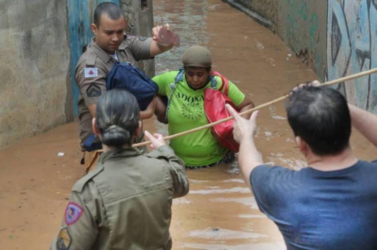 Policiais ajudam a resgatar vítimas em áreas alagadas.