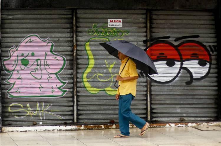 Homem em primeiro plano com guarda-chuva, passando em portão com grafites. Praia de Iracema, Fortaleza.
