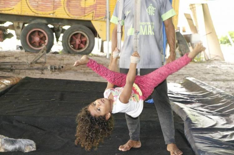 A pequena Rairiane não perde a oportunidade de brincar com o tecido de circo