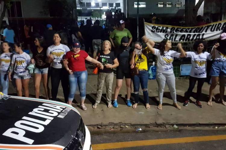 Mulheres de PMs fazem oração em frente ao 18° batalhão da Polícia Militar na noite desta quinta-feira, 20