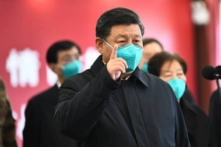 This photo released on March 10, 2020 by China's Xinhua News Agency shows Chinese President Xi Jinping wearing a mask as he waves to a coronavirus patient and medical staff via a video link at the Huoshenshan hospital in Wuhan, in China's central Hubei province on March 10, 2020.