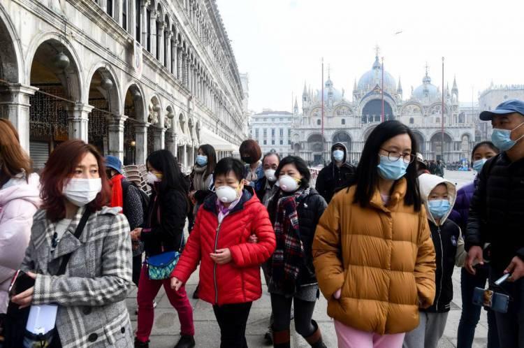 24 de fevereiro de 2020, Turistas usando máscaras protetoras visitam a Piazza San Marco, em Veneza