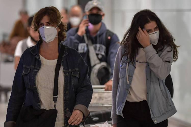 Passageiros que usam máscaras como medida de precaução para evitar a contração do novo coronavírus, COVID-19, chegam em um voo da Itália no Aeroporto Internacional de Guarulhos. (Foto: Nelson ALMEIDA / AFP)