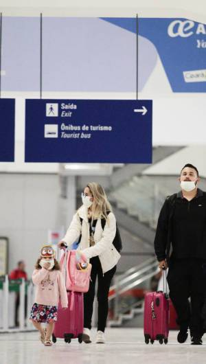 Pessoas com máscaras embarcando e desembarcando de vôos internacionais no Aeroporto Pinto Martins, em Fortaleza